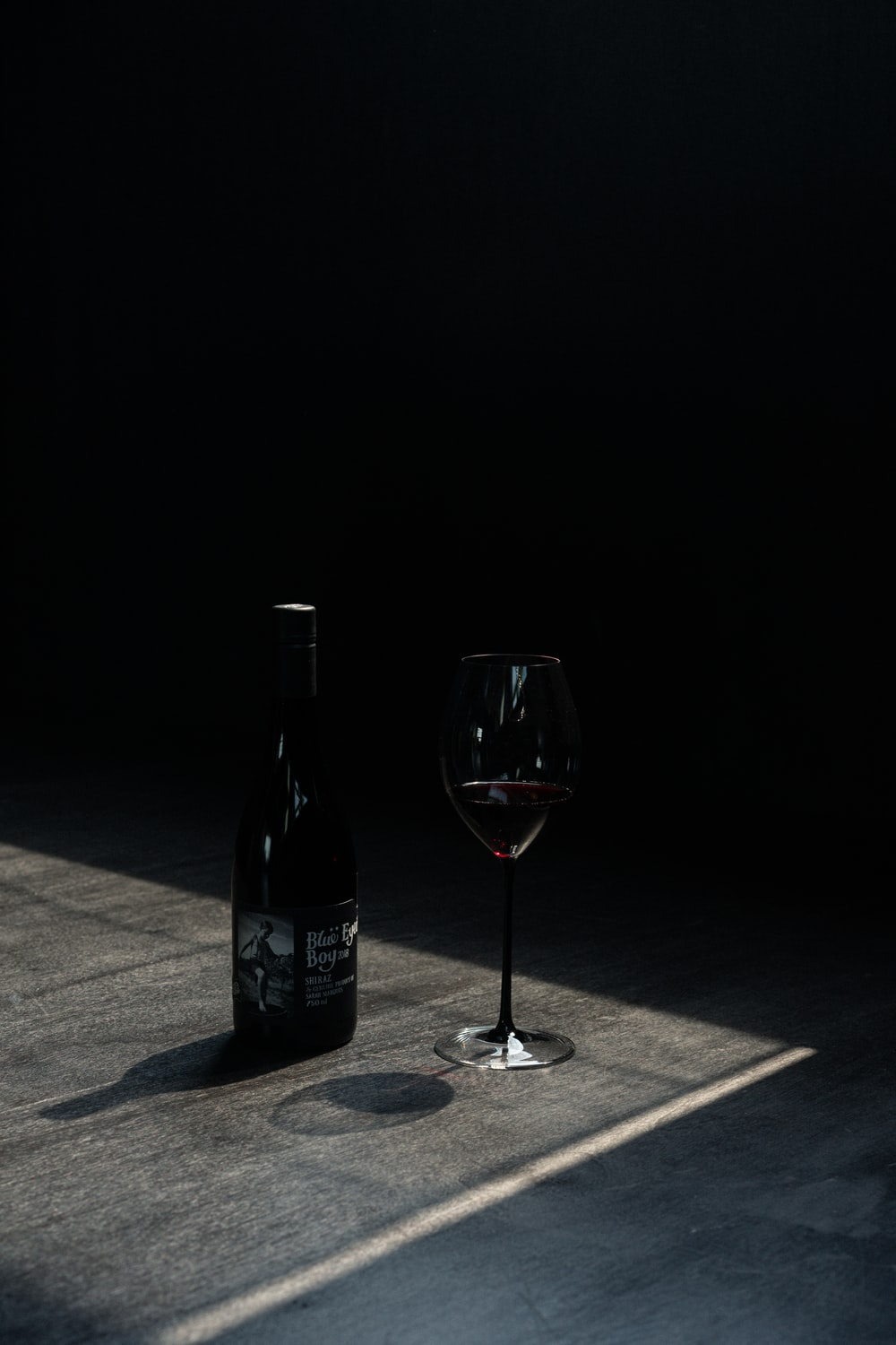 wine bottle beside wine glass on table