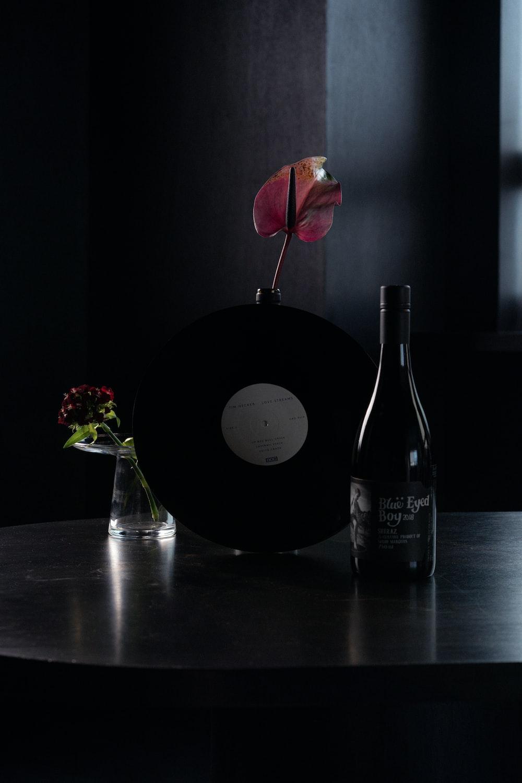 black wine bottle beside red rose
