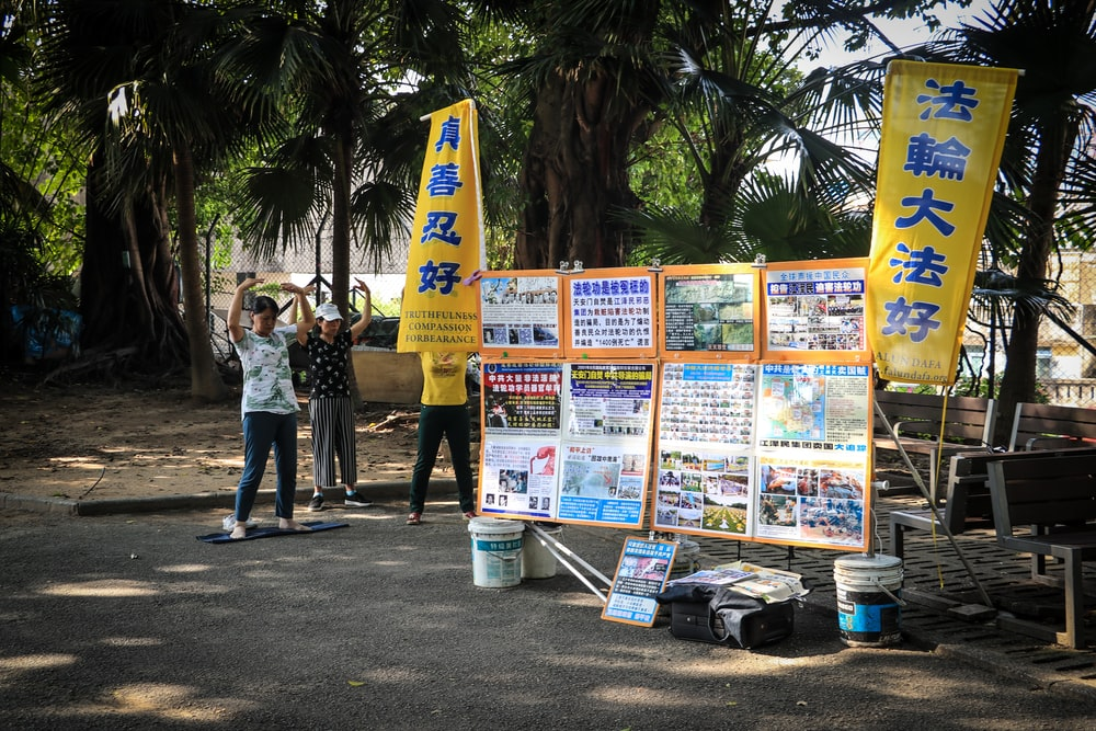 people standing near yellow and white signage during daytime