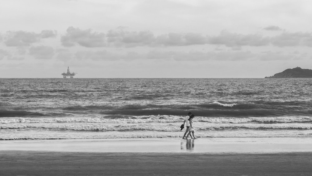 grayscale photo of man and woman walking on beach
