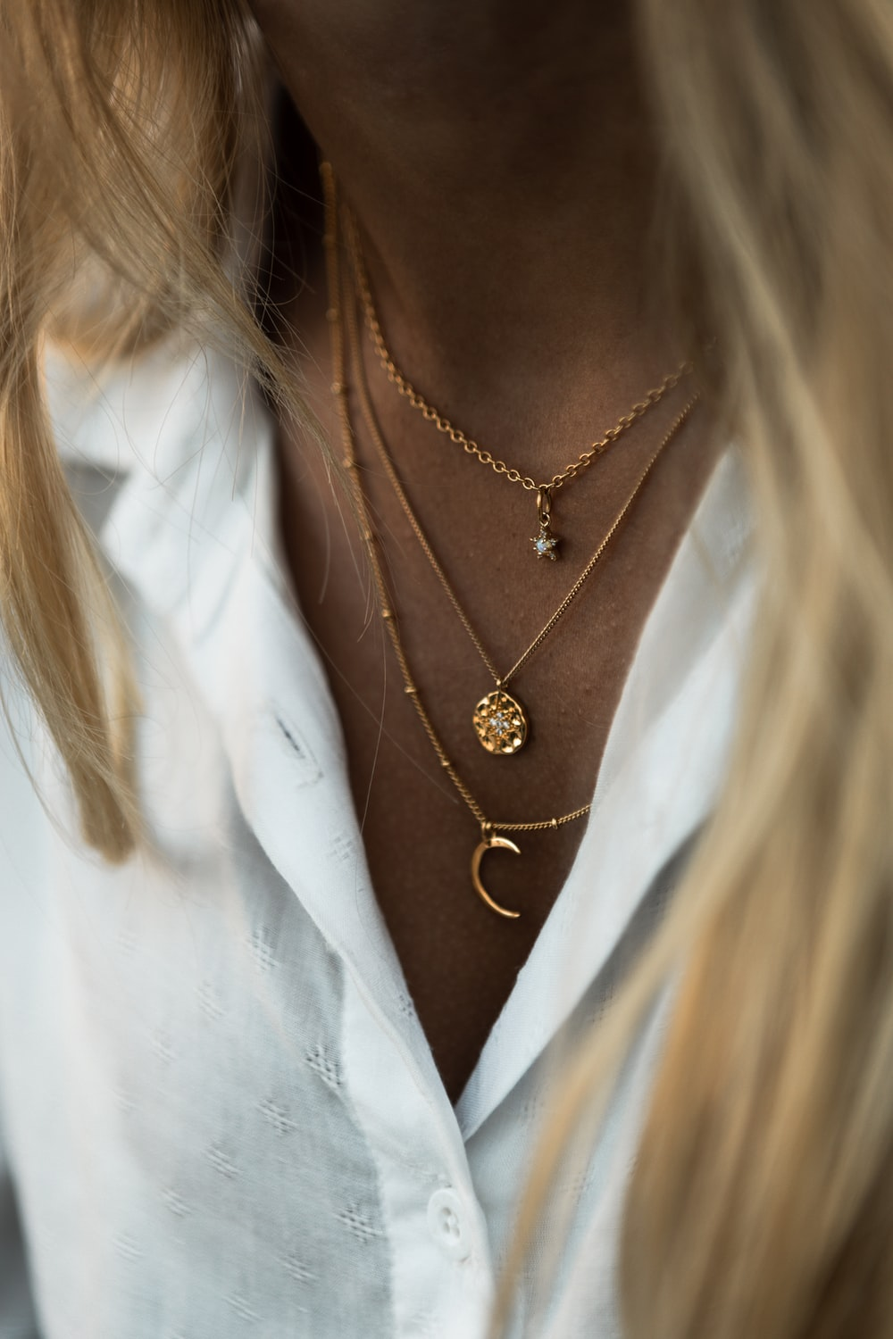 woman wearing gold necklace and white shirt