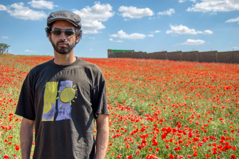 man in grey crew neck t-shirt standing on red flower field during daytime