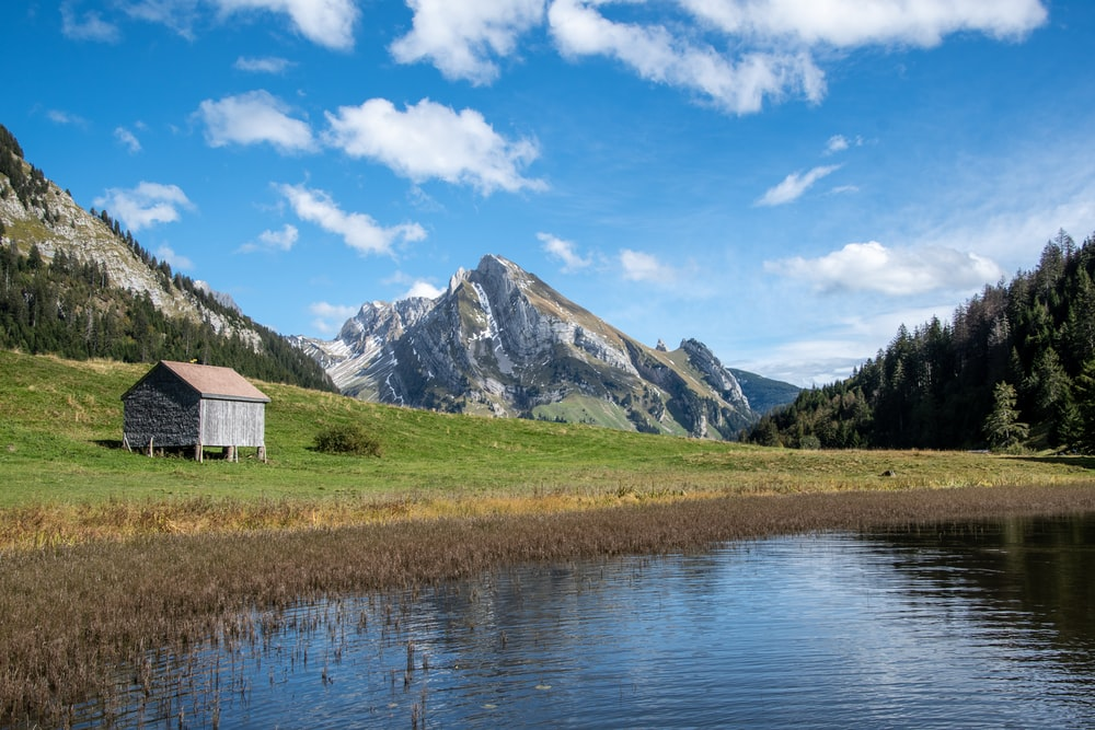 white and brown house near lake and green grass field and mountain under blue sky and