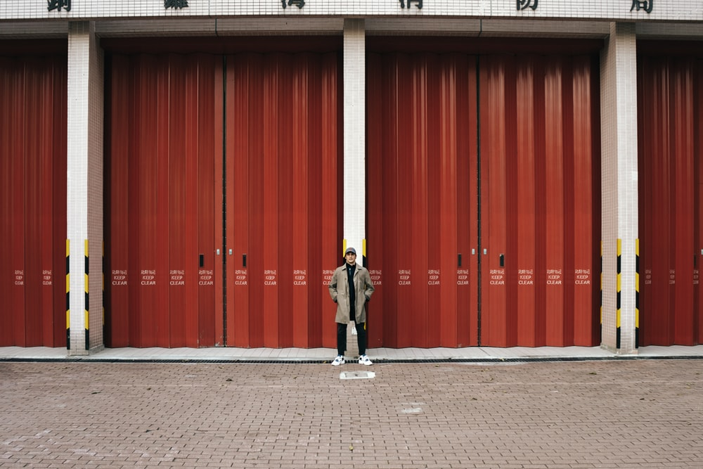 man in black jacket and black pants standing in front of red wall