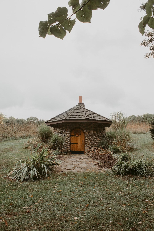 brown wooden house near green grass field during daytime