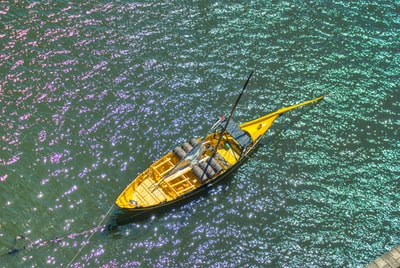 Yellow boat over brilliant water during day time