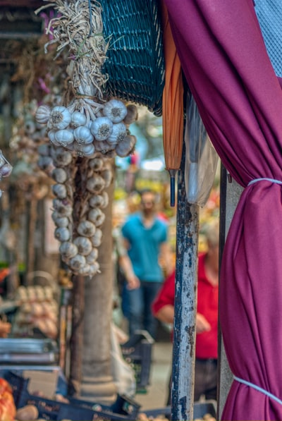 bunch of garlic hanging from a market stall