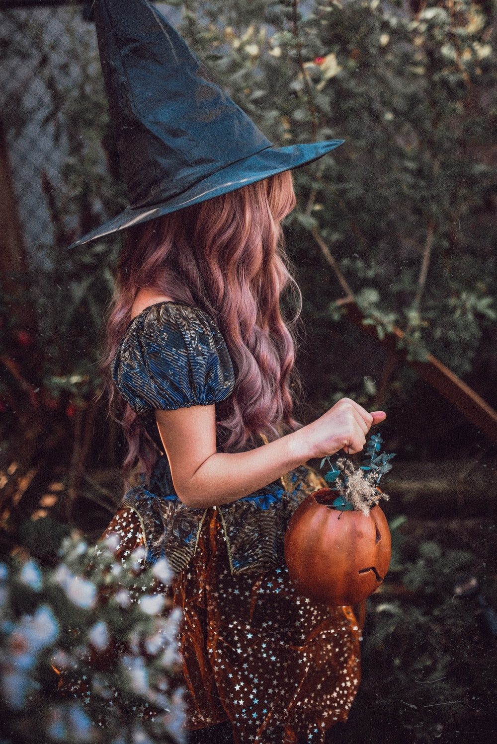 woman in black hat and brown dress holding pumpkin
