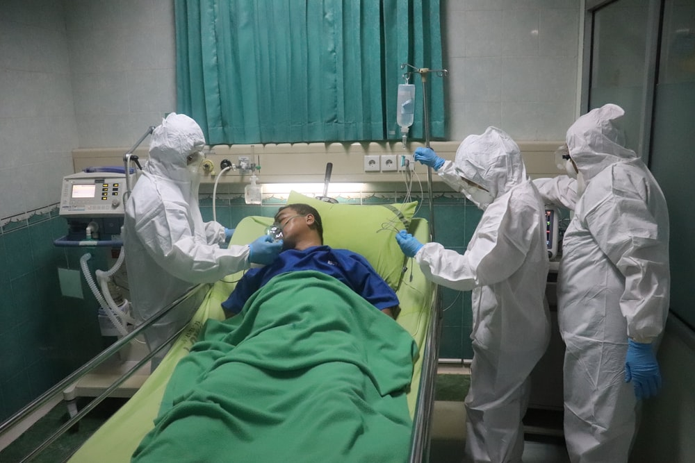 man in white scrub suit lying on hospital bed