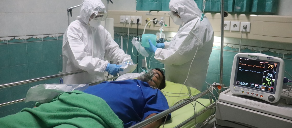 man in white medical scrub lying on hospital bed