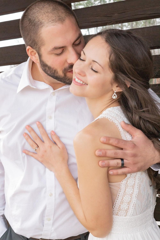 man in white dress shirt kissing woman in white sleeveless dress