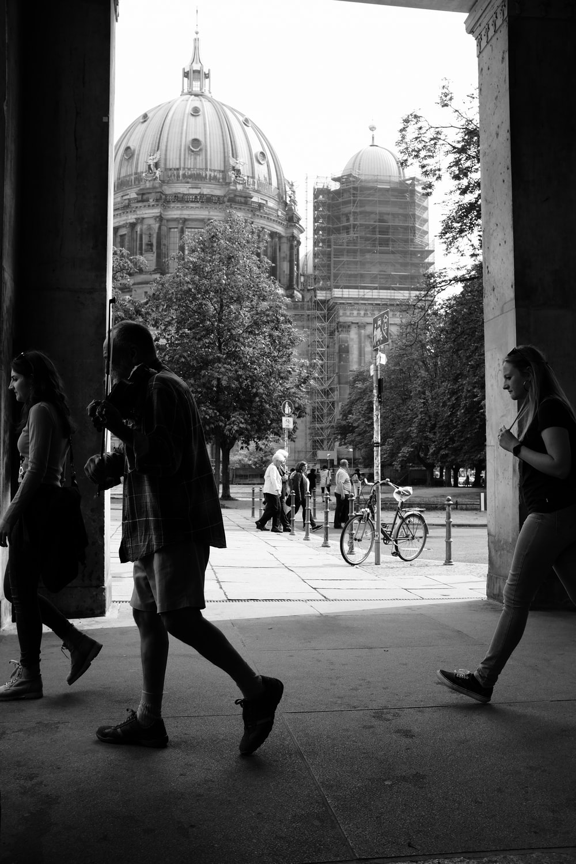 grayscale photo of man and woman walking on sidewalk