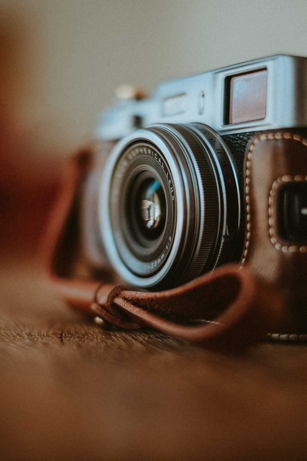 black and silver camera lens on brown leather strap