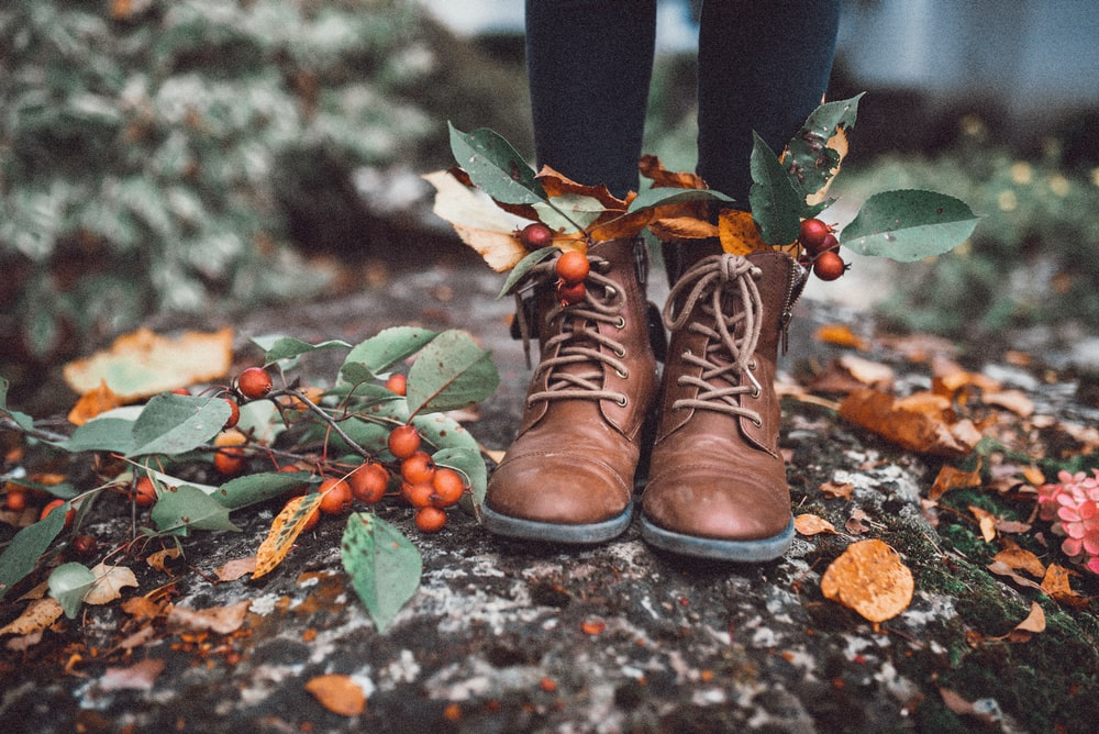 person wearing brown leather boots standing on ground with green leaves