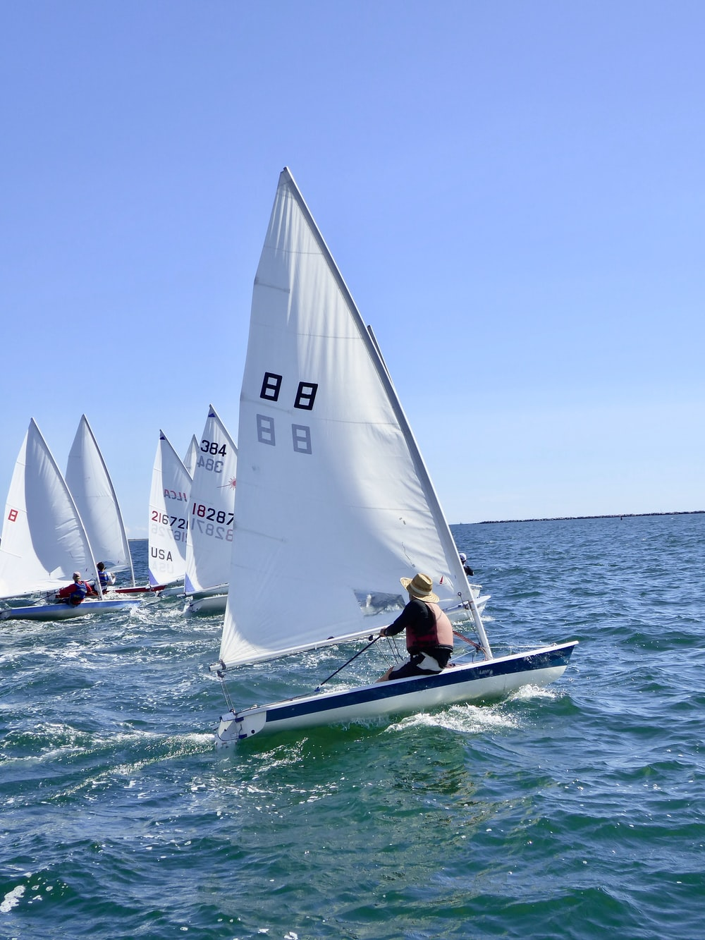 2 white sail boats on sea during daytime