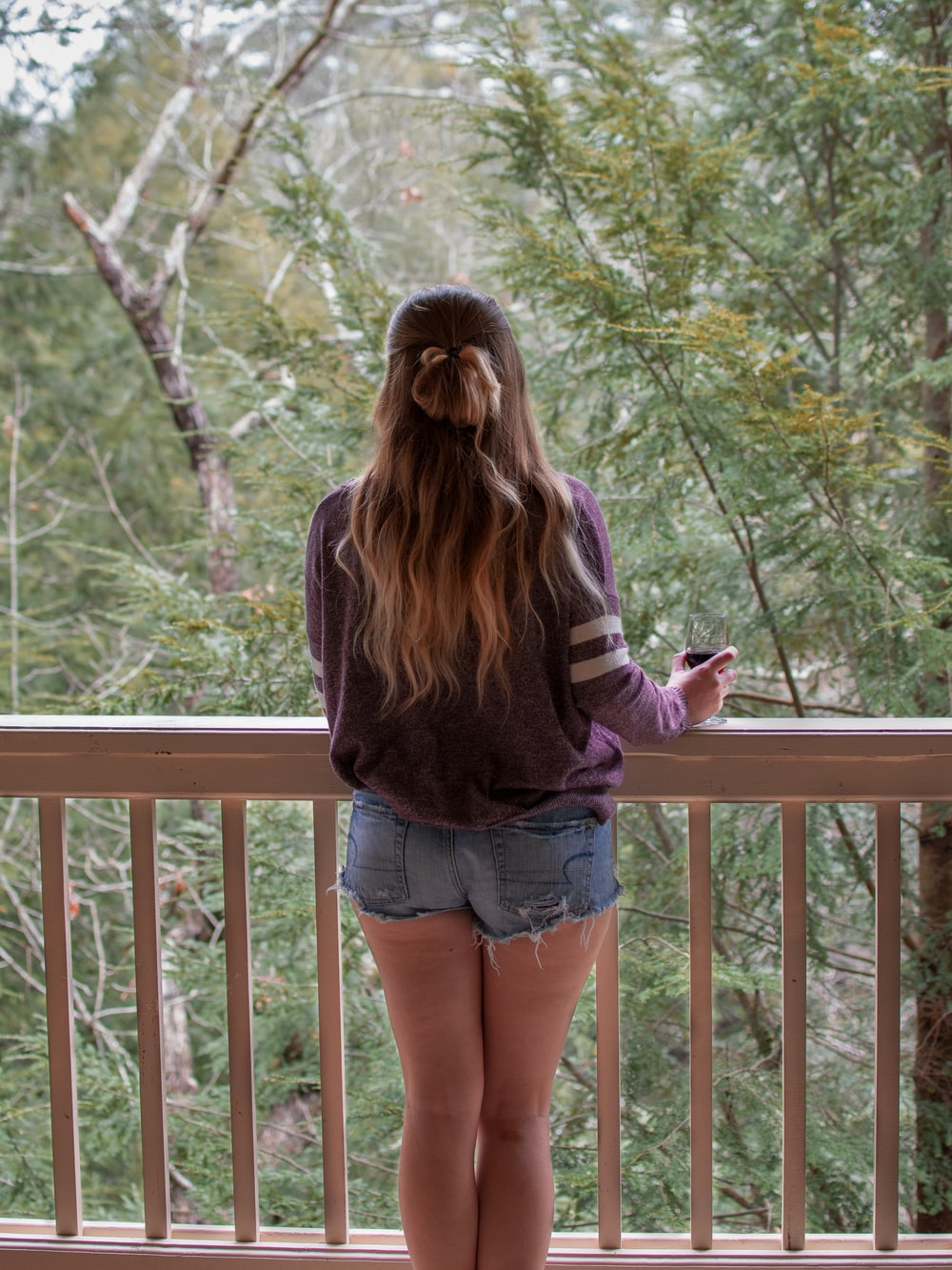 woman in purple long sleeve shirt and blue denim shorts standing on brown wooden bridge during