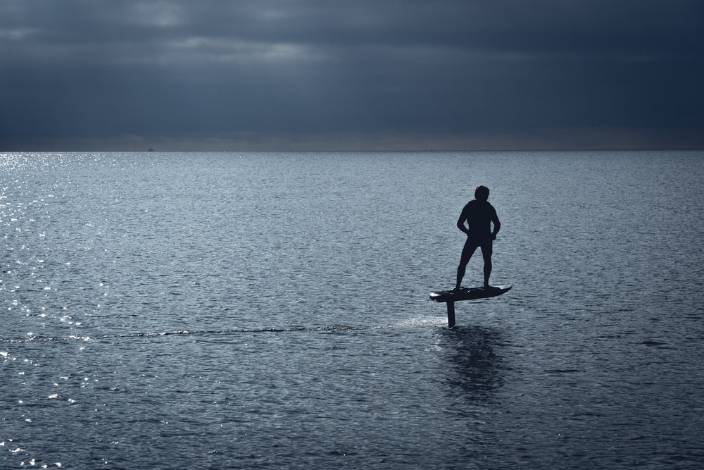 man in black wet suit standing on brown wooden paddle board during daytime