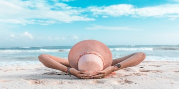woman in brown sun hat lying on sand during daytime