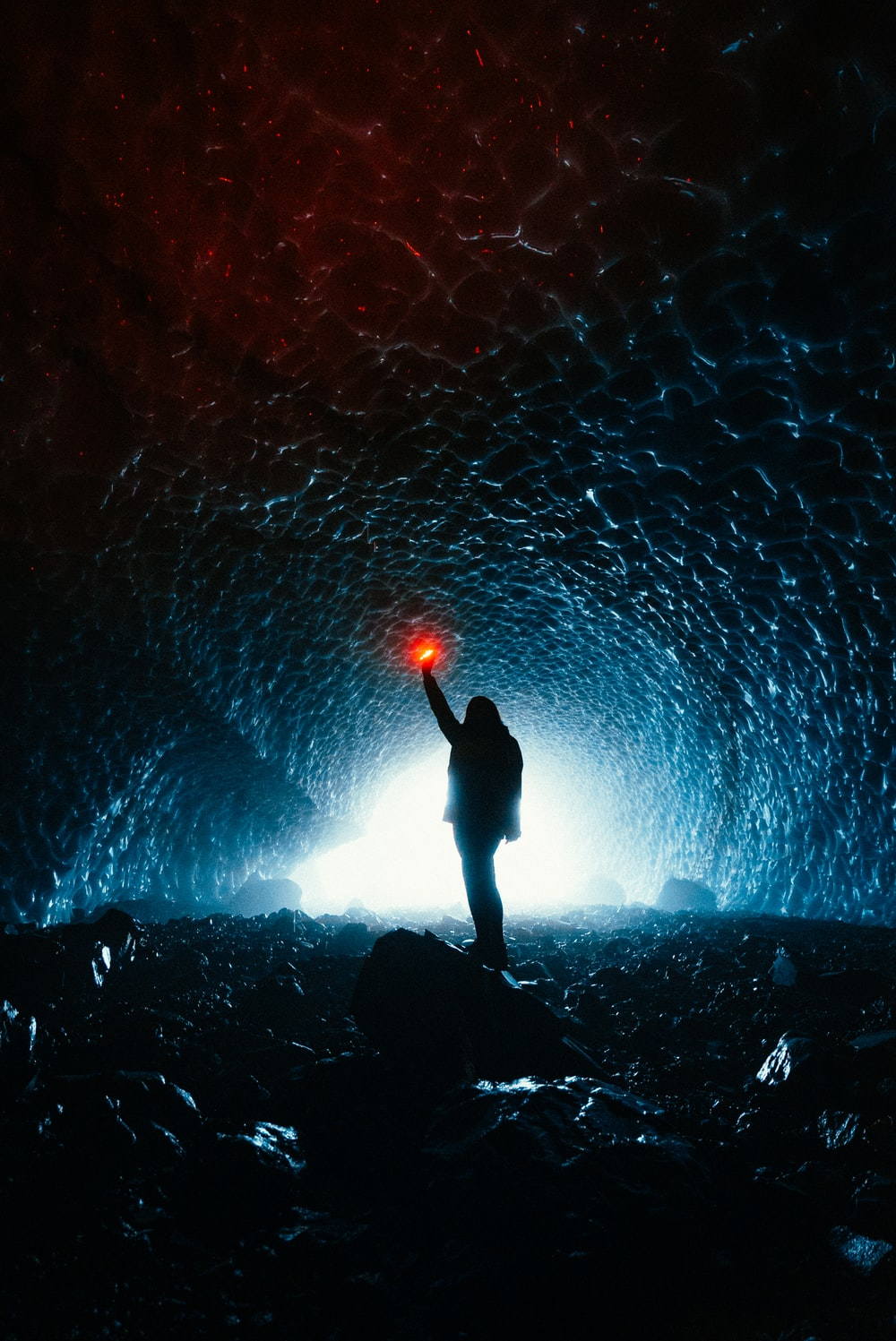 silhouette of person standing on rock with blue lights