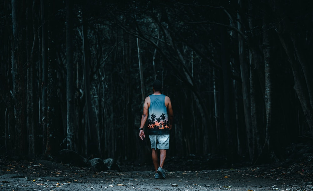 man in blue tank top and blue denim shorts standing in the middle of the forest