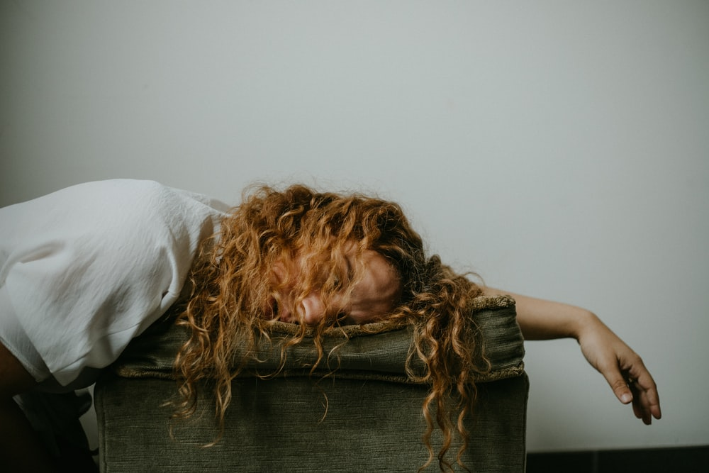 woman in white shirt lying on black textile