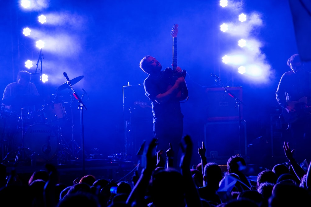 man in black t-shirt playing guitar on stage