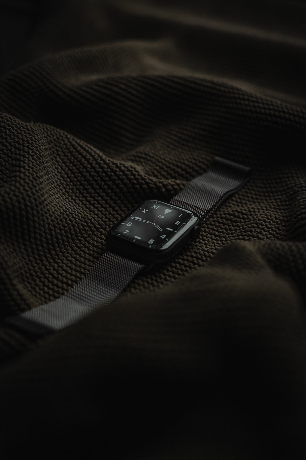 black apple watch on black and gray textile