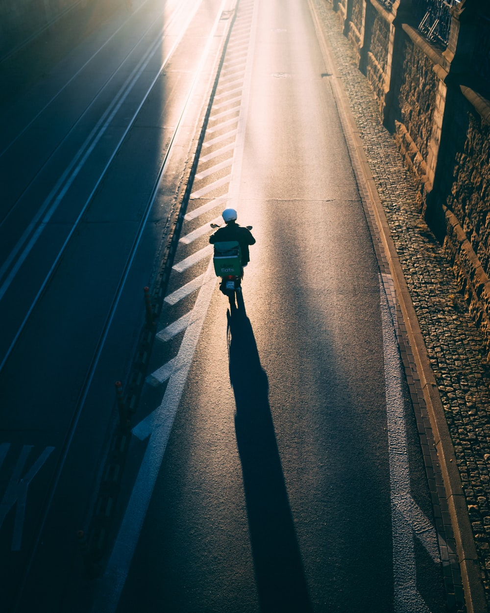 person in black jacket walking on train rail during night time