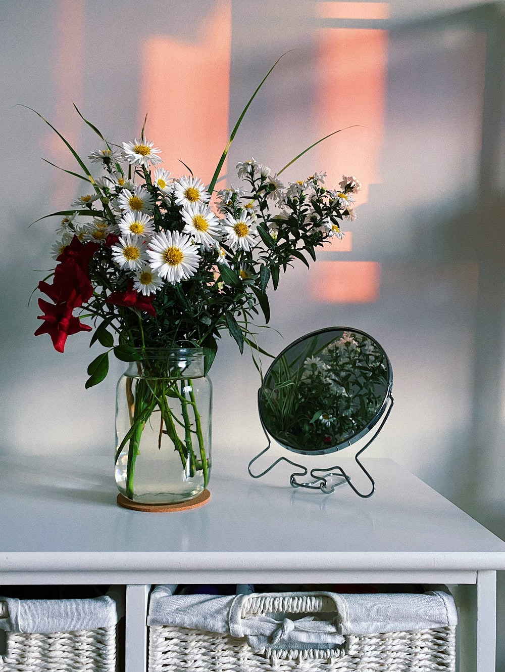 white and red flowers in clear glass vase