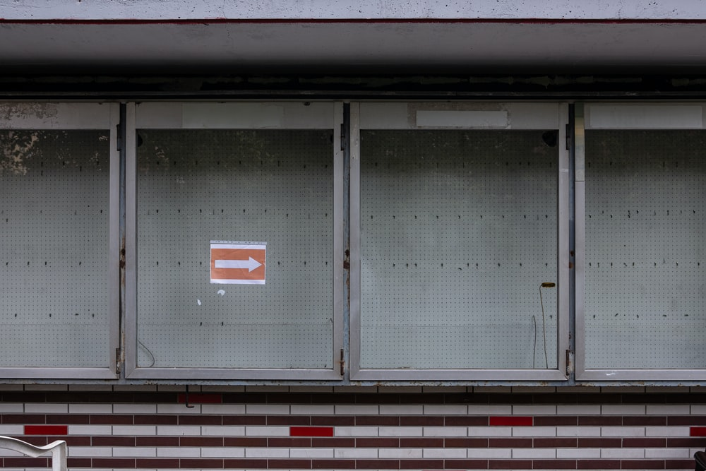 white and red arrow sign on gray steel door