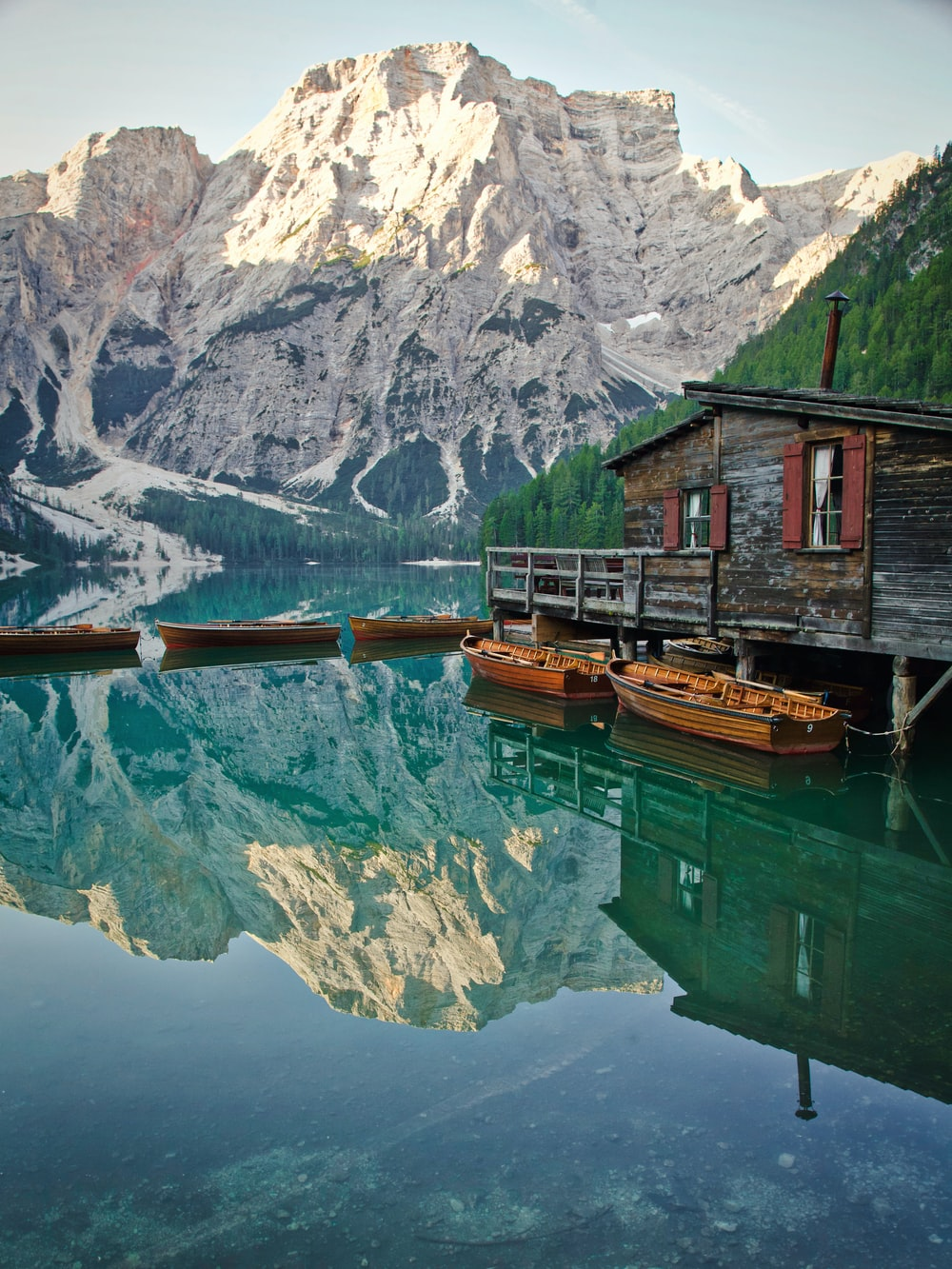 brown wooden house on green lake near snow covered mountain during daytime