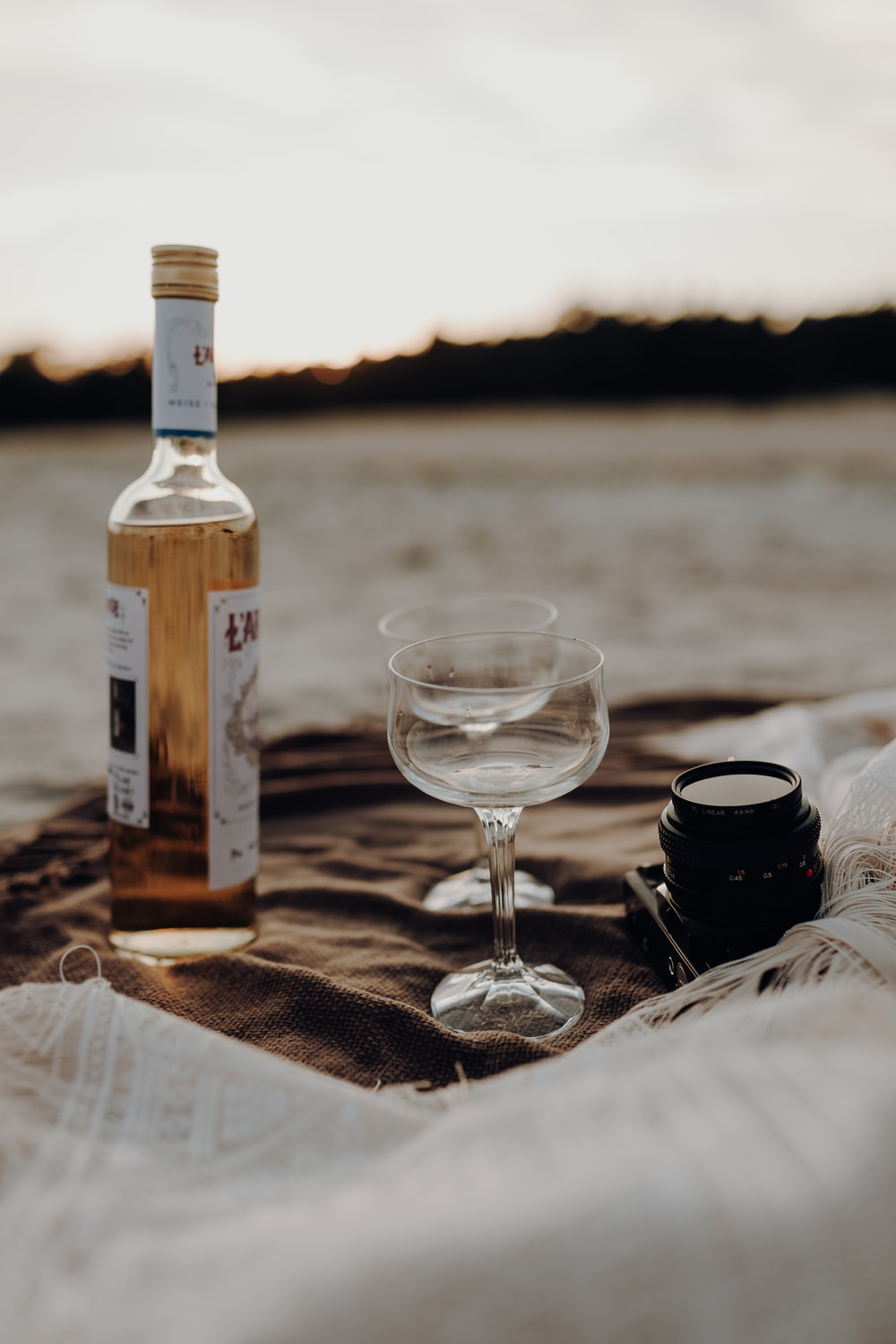 clear wine glass beside black ceramic mug on brown wooden table