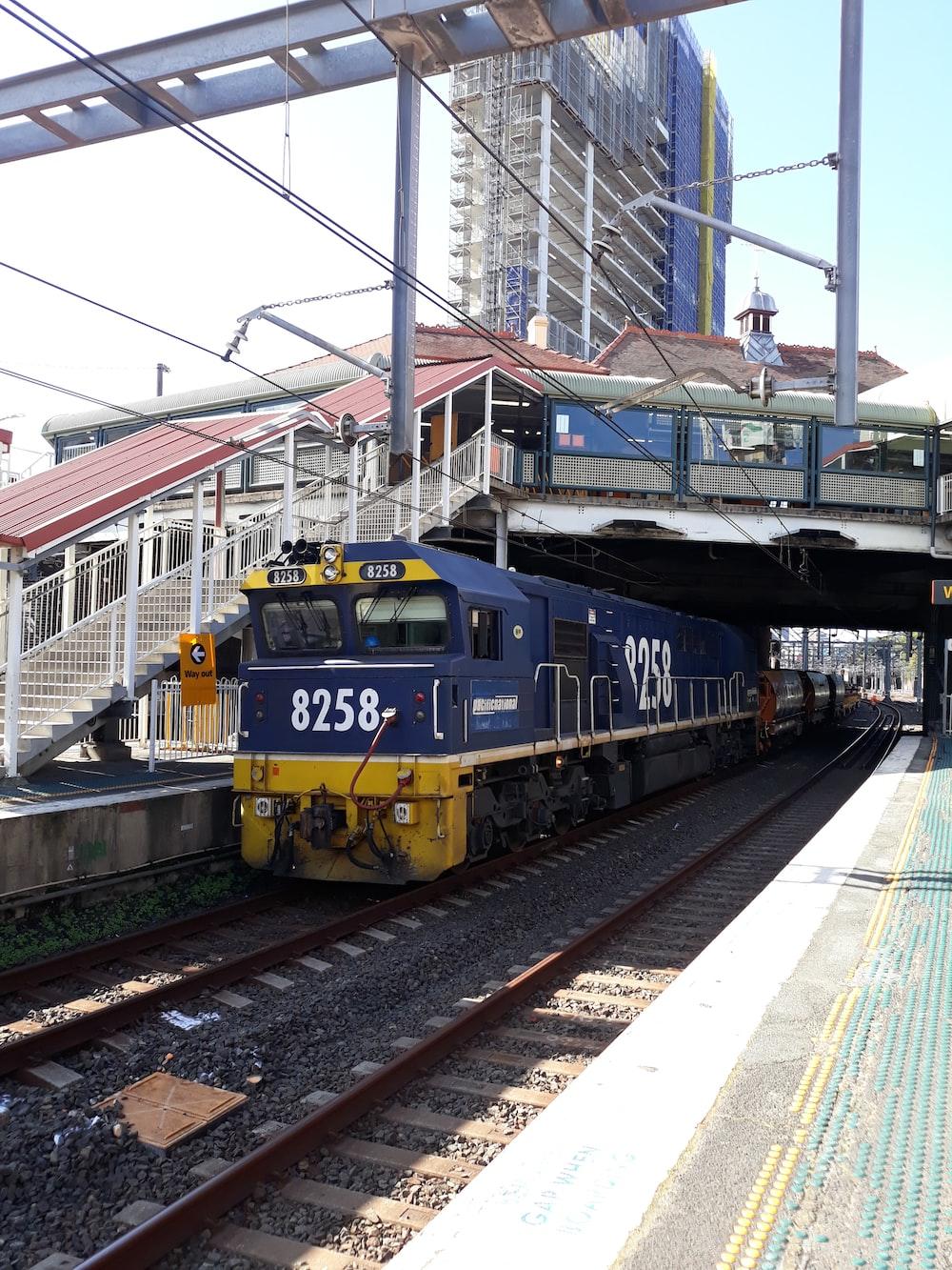 blue and yellow train on rail tracks