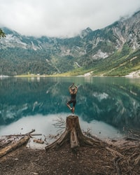 woman in black tank top and black shorts standing on brown log on lake during daytime