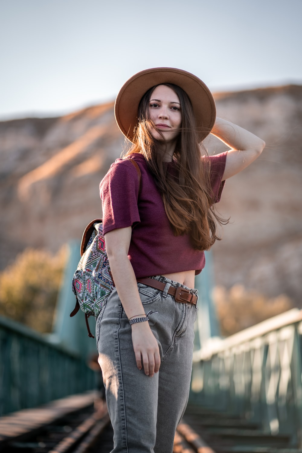 woman in red shirt and blue denim jeans wearing brown hat