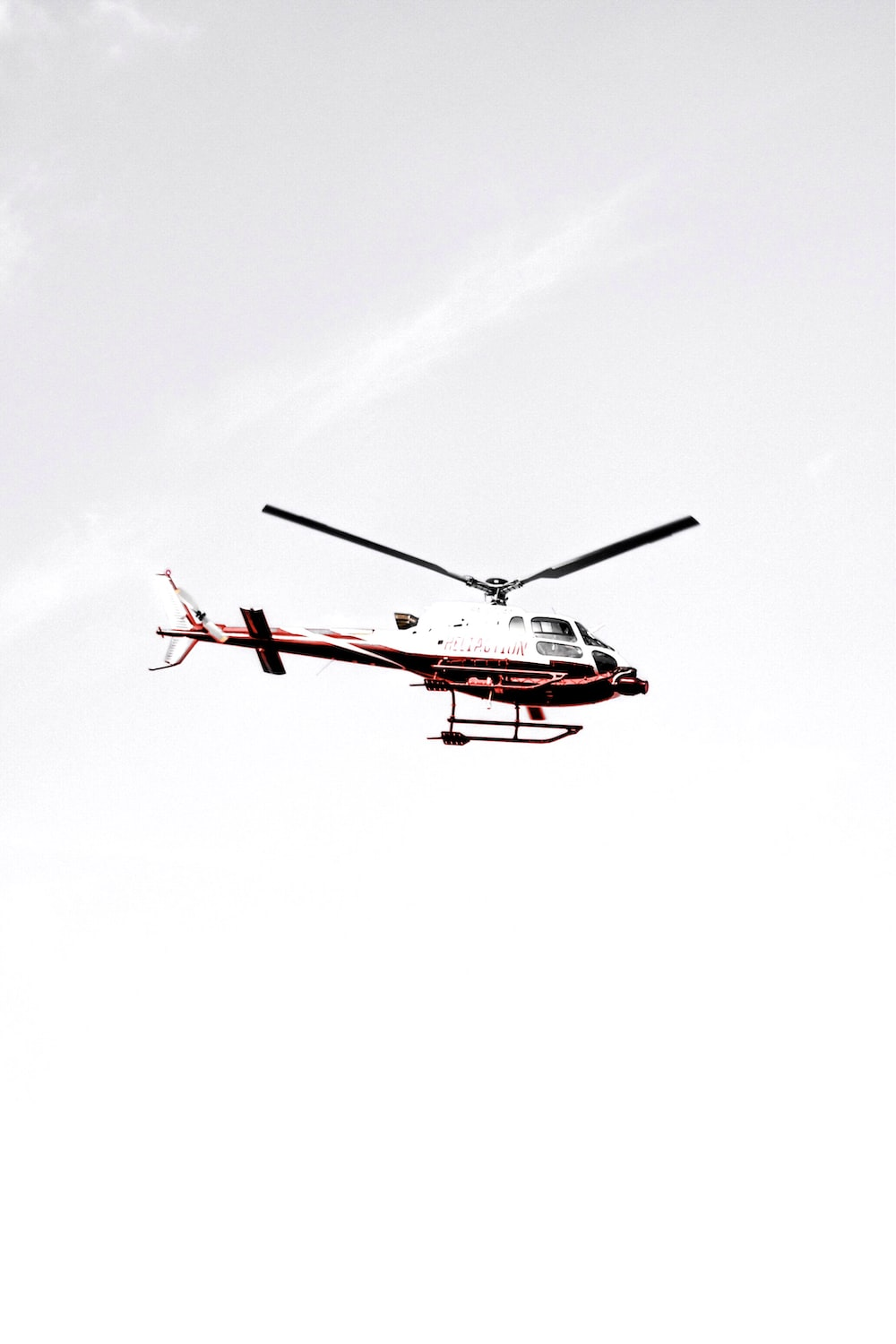 white and red helicopter flying in the sky