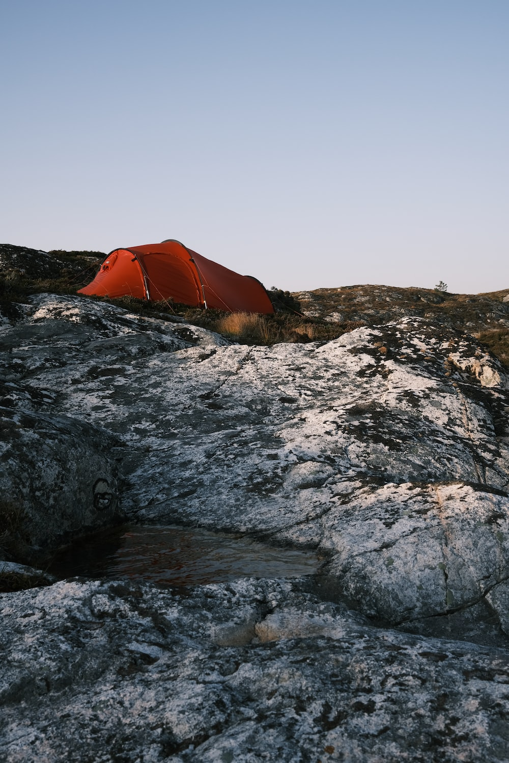 orange tent on rocky shore during daytime