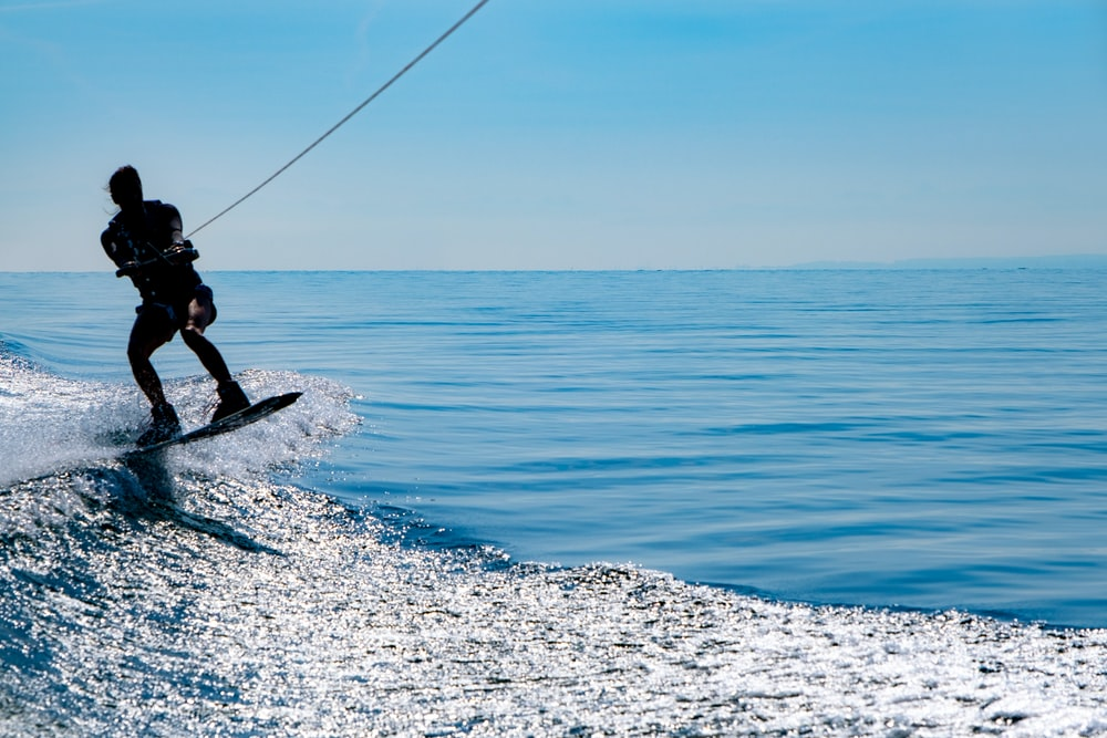 man in black wetsuit surfing on blue sea under blue sky during daytime