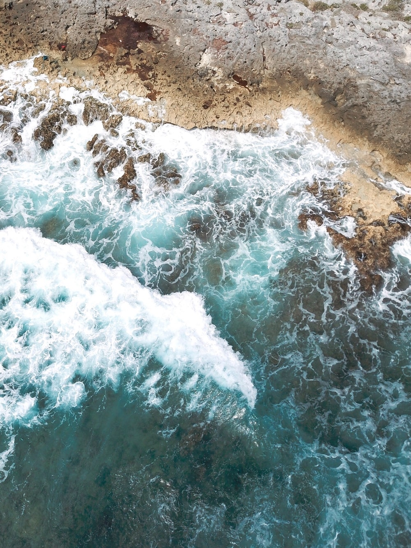water waves hitting brown sand during daytime