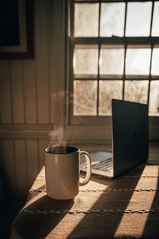 white ceramic mug beside silver macbook on table