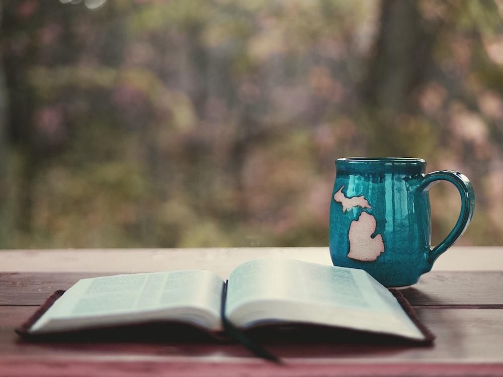 blue ceramic mug on book page