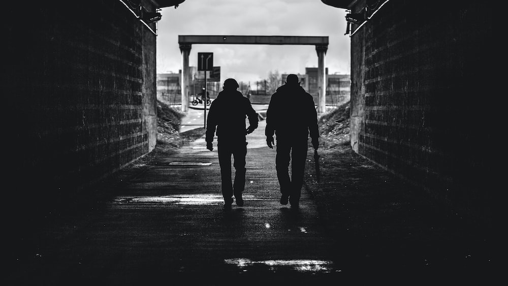 grayscale photo of man and woman walking on sidewalk