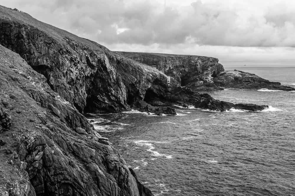 grayscale photo of rocky mountain beside sea