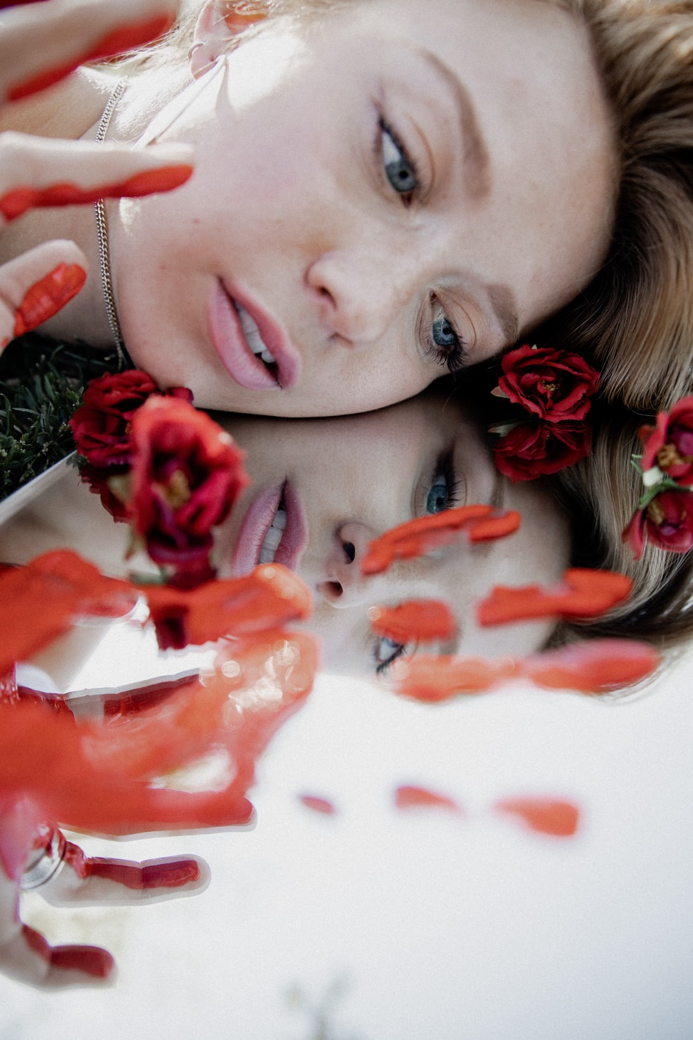 woman with red rose petals on her face