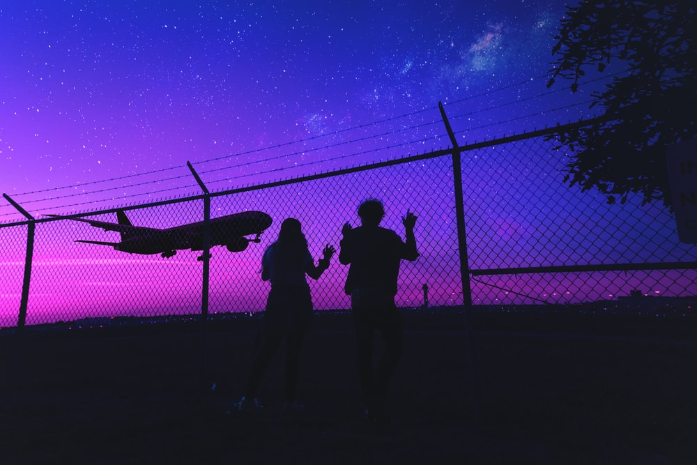 silhouette of 2 person standing beside fence during night time