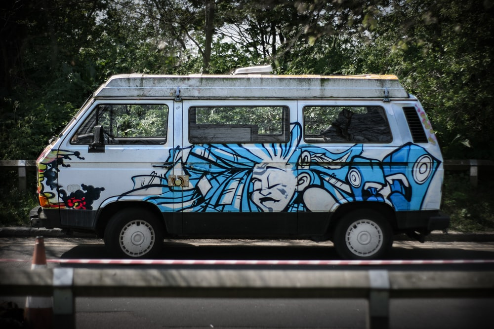blue and white van on road during daytime
