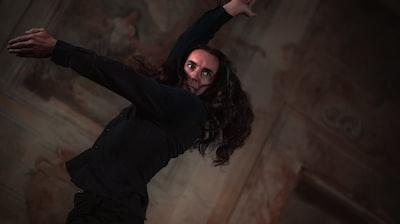 woman in black long sleeve shirt performance art teams background