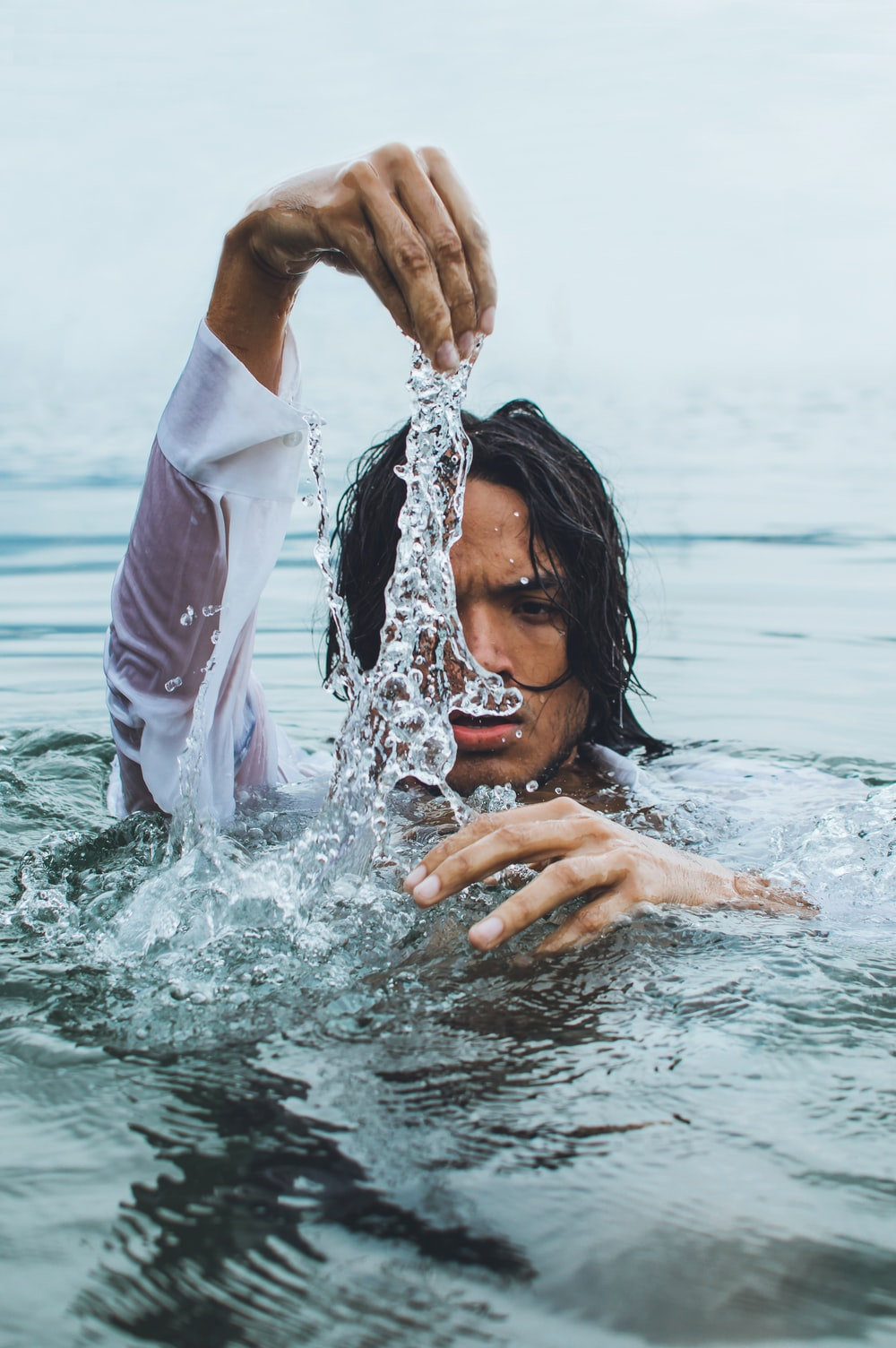 woman in white long sleeve shirt in water