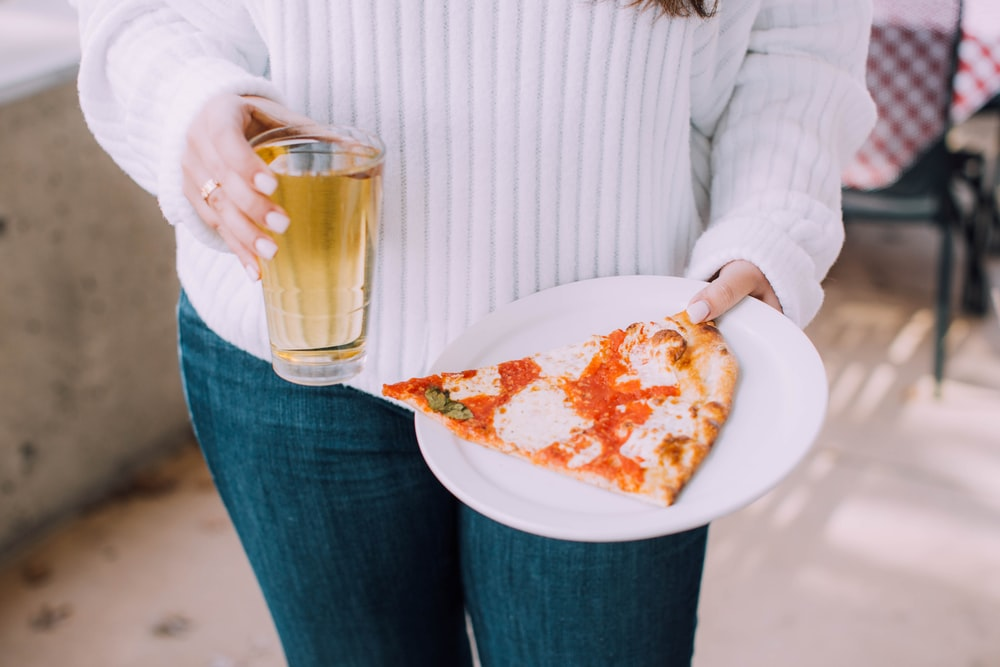 person holding white ceramic plate with pizza