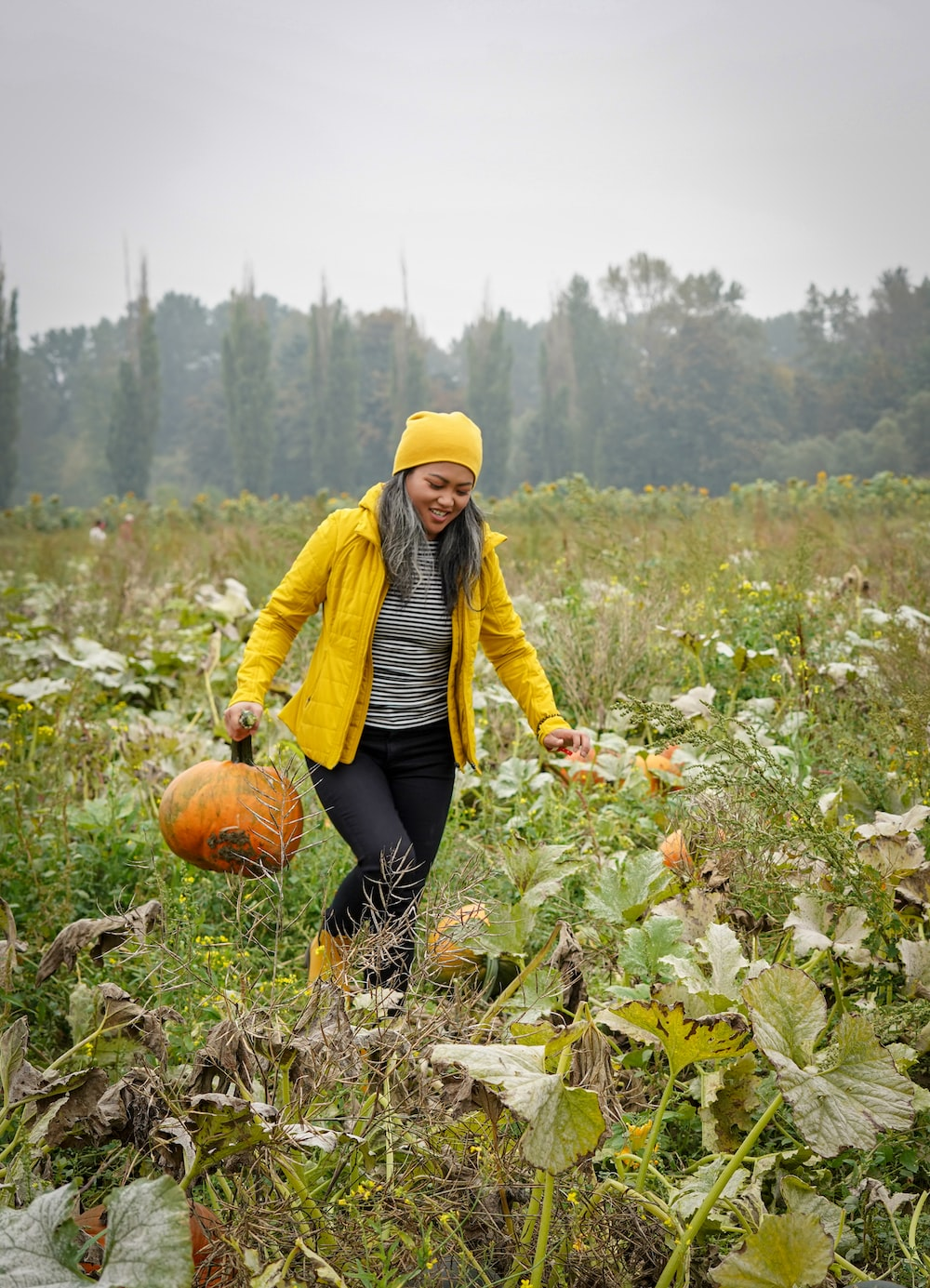 woman in yellow jacket and black pants sitting on pumpkin during daytime